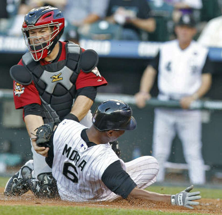 Rockies first baseman Melvin Mora slides into home before the tag by Astros catcher Humberto Quintero. Photo: Ed Andrieski, AP