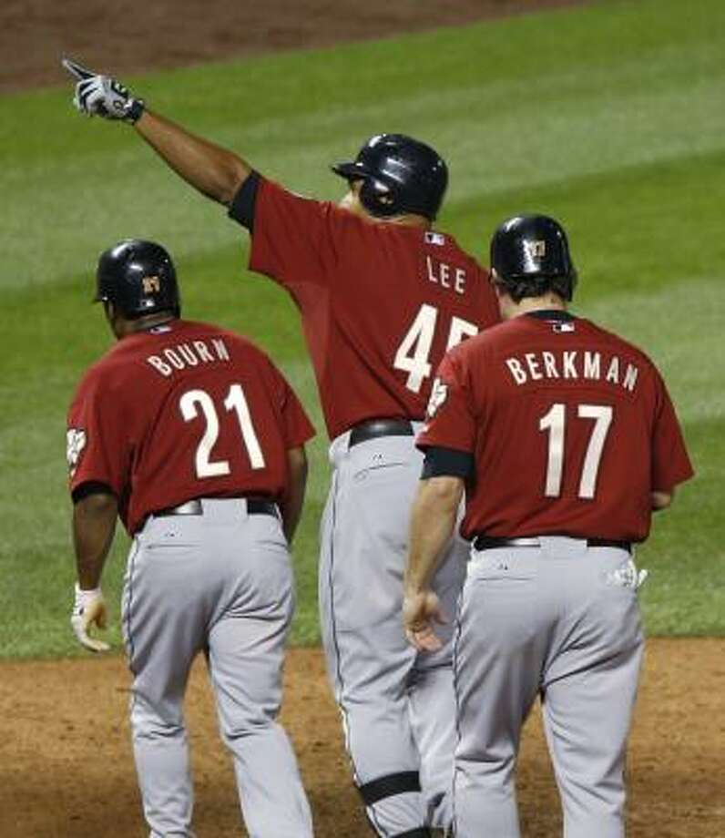 Astros left fielder Carlos Lee points to the stands after hitting a grand slam and driving in Michael Bourn, left, Lance Berkman, right, and Tommy Manzella, not pictured, in the 10th inning. Photo: Ed Andrieski, AP