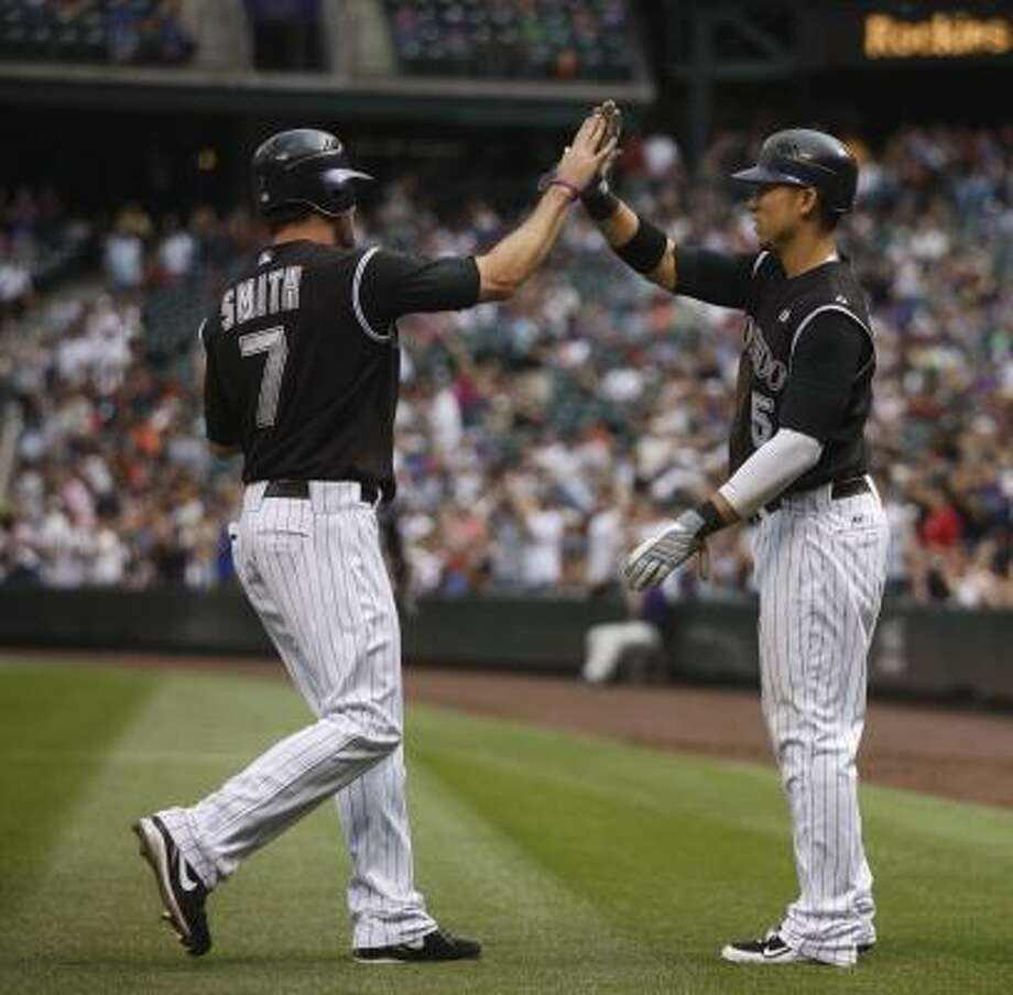 Rockies left fielder Seth Smith, left, and center fielder Carlos Gonzalez opened the scoring after coming home on a double by Troy Tulowitzki in the first inning. Photo: David Zalubowski, AP