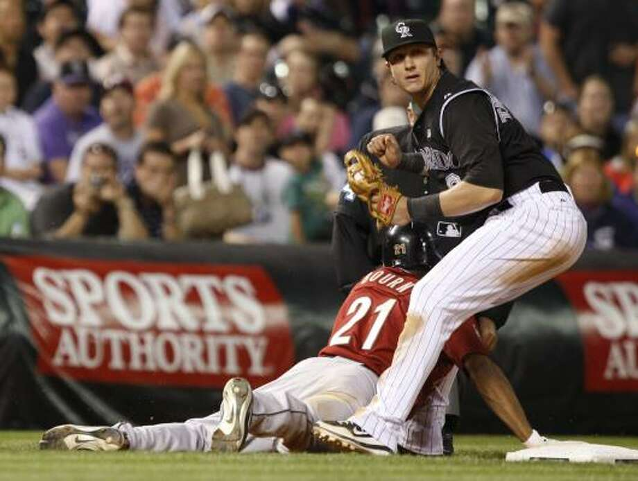 Astros pinch-hitter Michael Bourn dives safely back into third base as Rockies shortstop Troy Tulowitzki fields a throw. Photo: David Zalubowski, AP