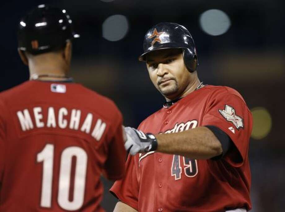 Astros first base coach Bobby Meacham congratulates Carlos Lee after his single in the eighth. Photo: David Zalubowski, AP