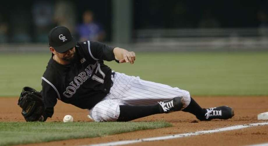 Rockies first baseman Todd Helton tumbles off first base while trying to field a throw from second baseman Clint Barmes. Photo: David Zalubowski, AP