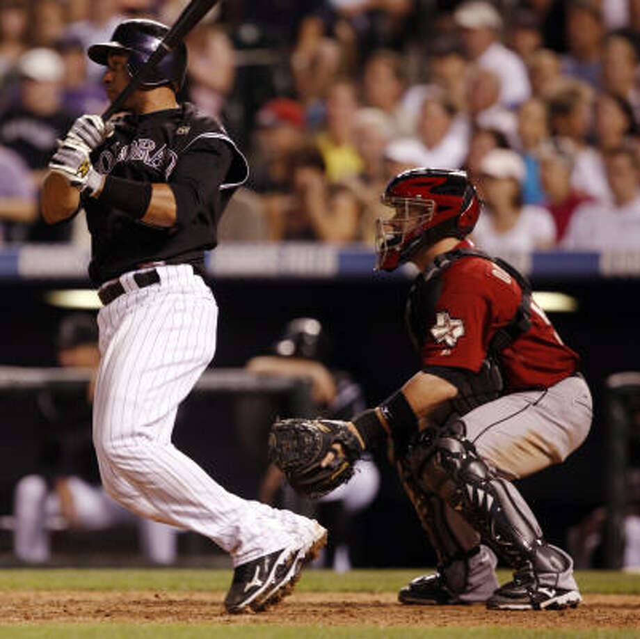 Rockies catcher Miguel Olivo, left, follows the flight of his triple, which scored a run. Photo: David Zalubowski, AP