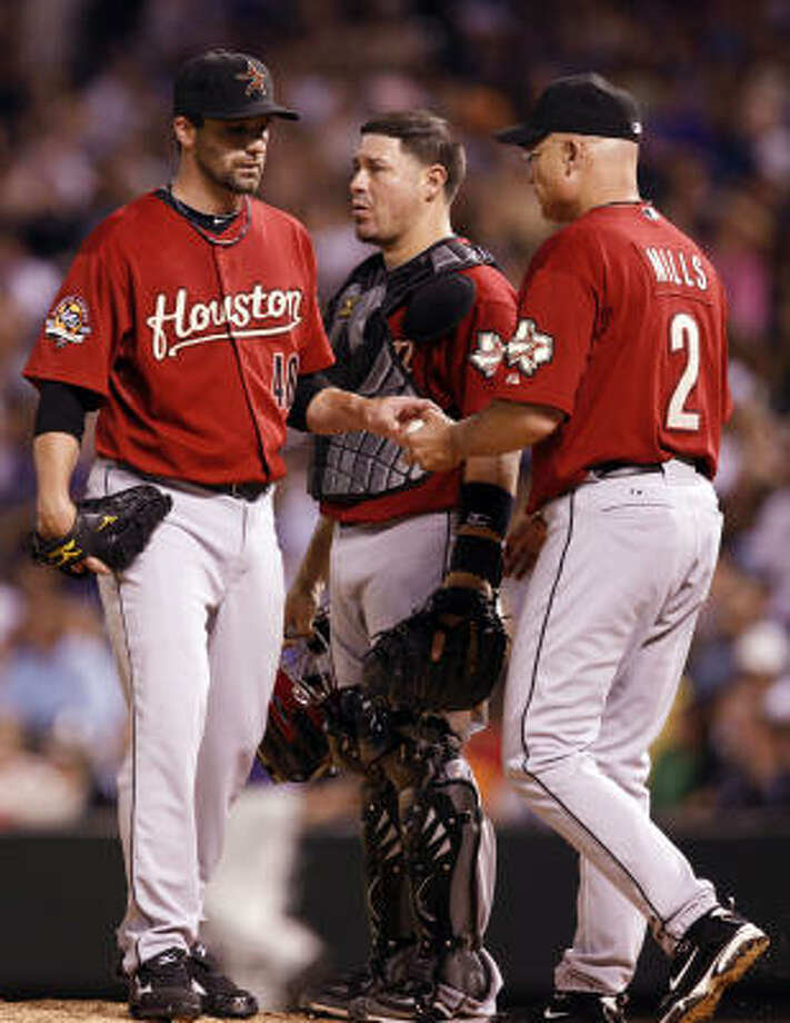 Astros relief pitcher Tim Byrdak, left, hands over the ball to manager Brad Mills, right, as catcher Humberto Quintero, center, watches. Photo: David Zalubowski, AP