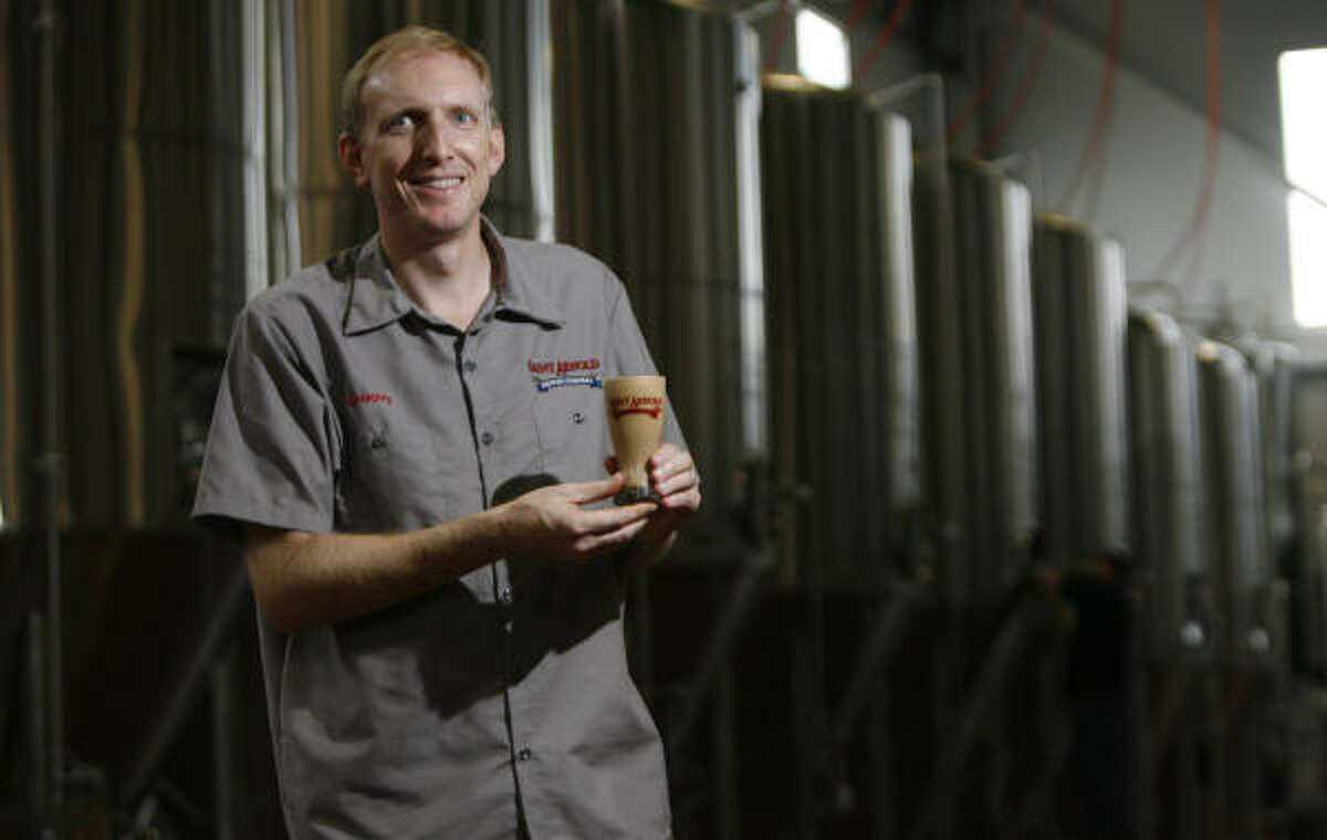 Brock Wagner, the founder of Saint Arnold Brewing Co., holds a glass full of yeast.