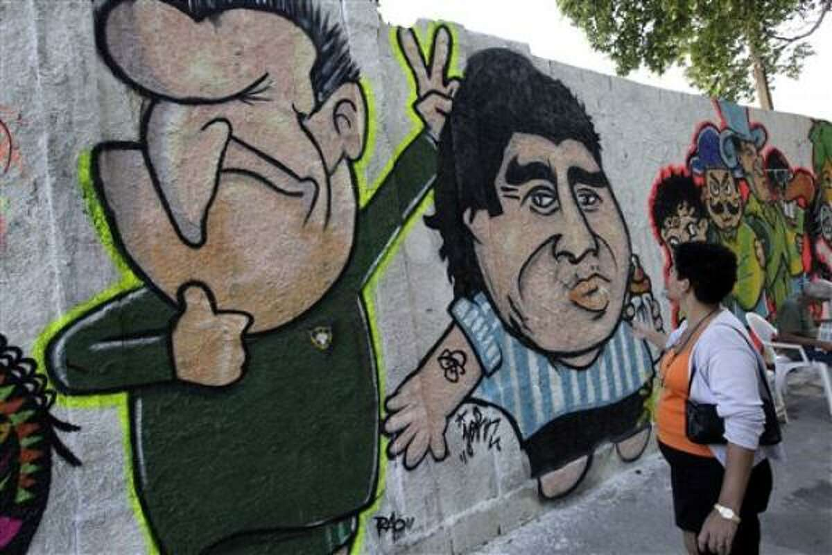 Una mujer observa un graffiti de los técnicos de Brasil, Dunga (izq), y Argentina, Diego Maradona, en un muro del barrio de Vila Isabel, en Río de Janeiro. Ambos deben demostrar su nivel como técnicos en la Copa Mundial.