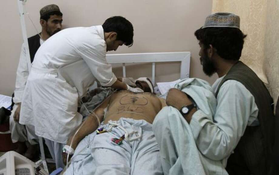 A medical staffer helps a wounded man at a hospital following a blast at a wedding party in Kandahar city, Afghanistan, Thursday, June 10, 2010. NATO blamed the Taliban for the suicide attack that killed at least 40 Afghan wedding guests in an area where U.S.-led troops are massing to drive insurgents from their fiefdom. Officials said a suicide bomber strapped with explosives had walked into on June 9 wedding party -- which relatives said was attended by members of an anti-Taliban militia -- and unleashed a deadly hail of ballbearings. At least 40 killed in Taliban suicide bombing at wedding in Afghanistan Photo: Allauddin Khan, AP