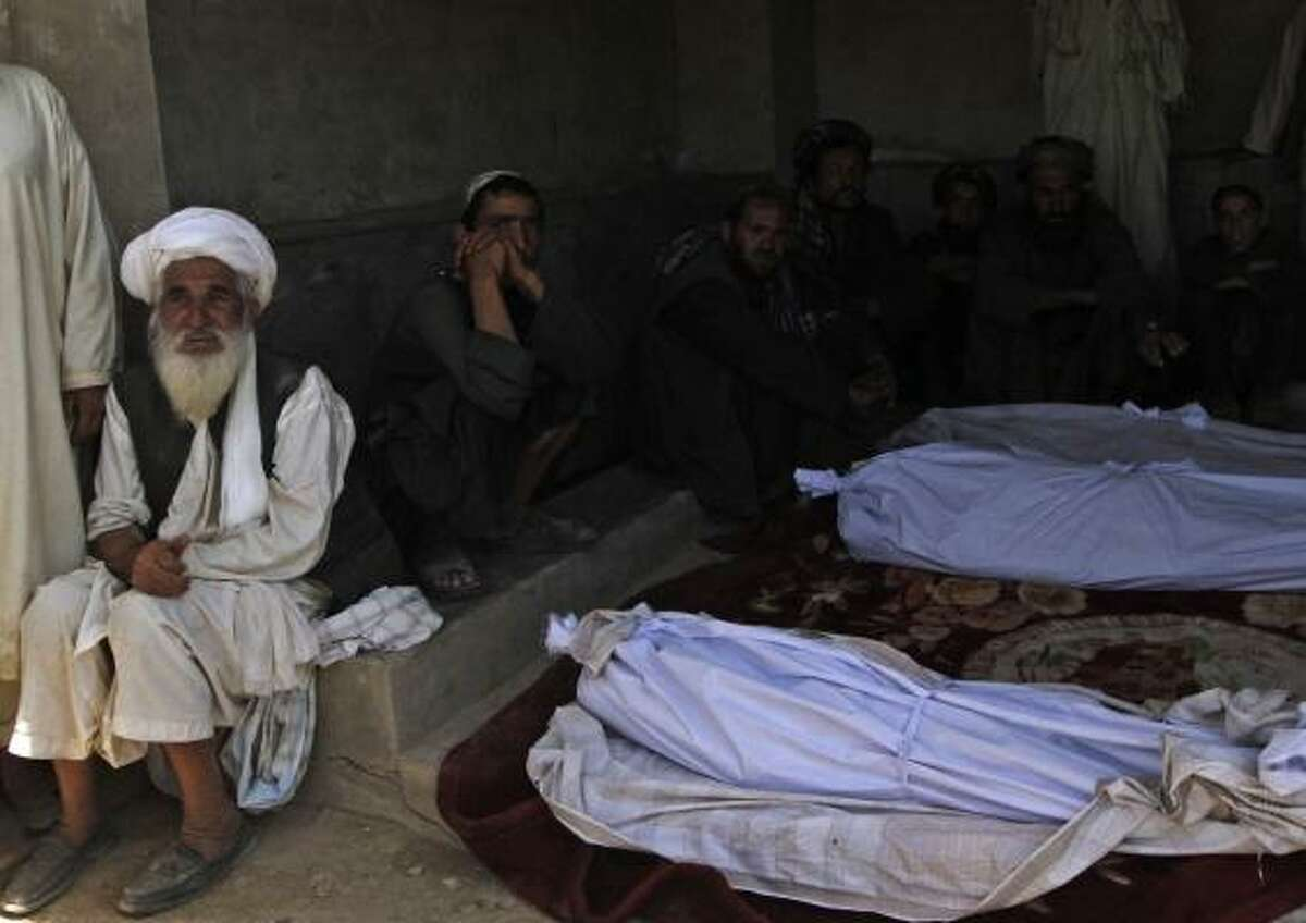 Afghan men sit around the bodies of people killed in a blast in Kandahar's Argandab district Thursday, June 10, 2010. NATO blamed the Taliban for the suicide attack that killed at least 40 Afghan wedding guests in an area where U.S.-led troops are massing to drive insurgents from their fiefdom. Officials said a suicide bomber strapped with explosives had walked into on June 9 wedding party -- which relatives said was attended by members of an anti-Taliban militia -- and unleashed a deadly hail of ballbearings. At least 40 killed in Taliban suicide bombing at wedding in Afghanistan