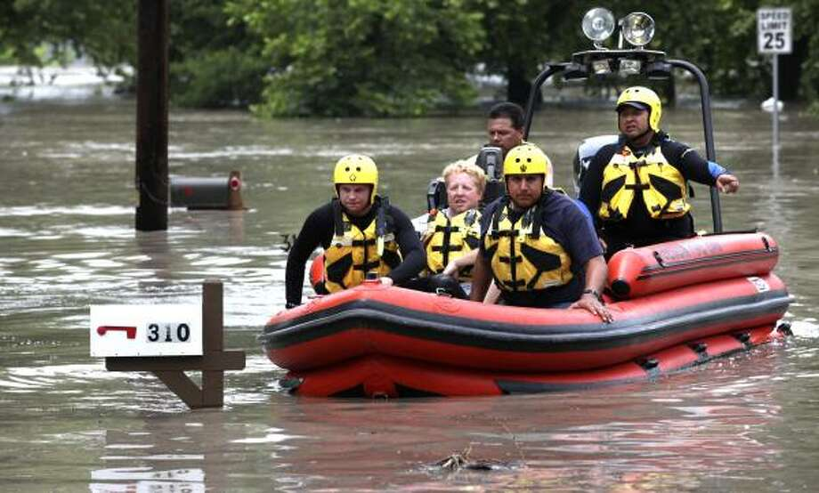 Members of the Seguin Fire Department rescue team retrieve David Miller from his flooded home in Pecan Cove Estates on Turtle Lane on the Guadalupe River just outside Seguin, Wednesday, June 9, 2010. Photo: Bob Owen, AP
