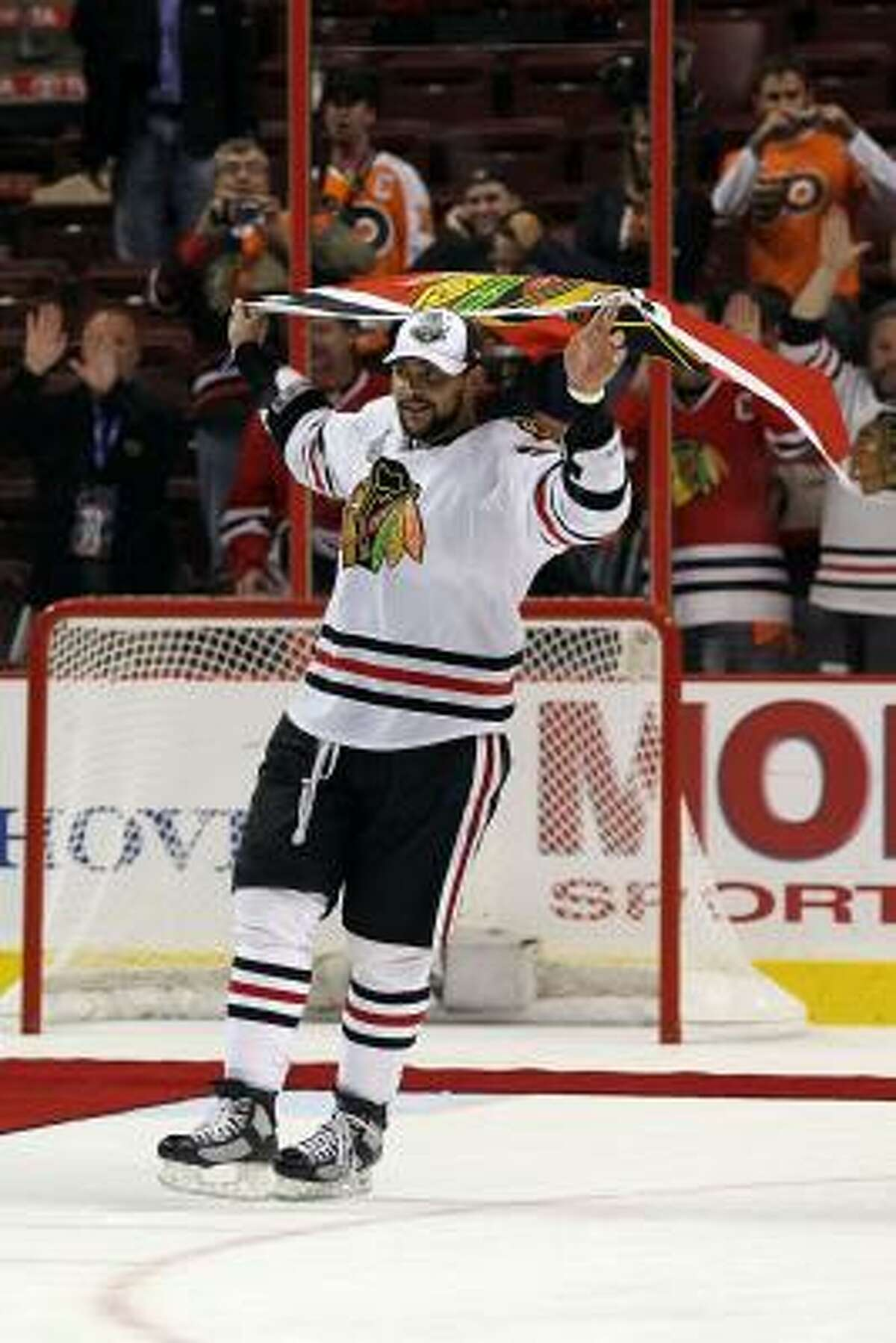 Dustin Byfuglien skates with the Blackhawks flag after teammate Patrick Kane scored the game-winning goal in overtime to defeat the Philadelphia Flyers 4-3 and win the Stanley Cup.