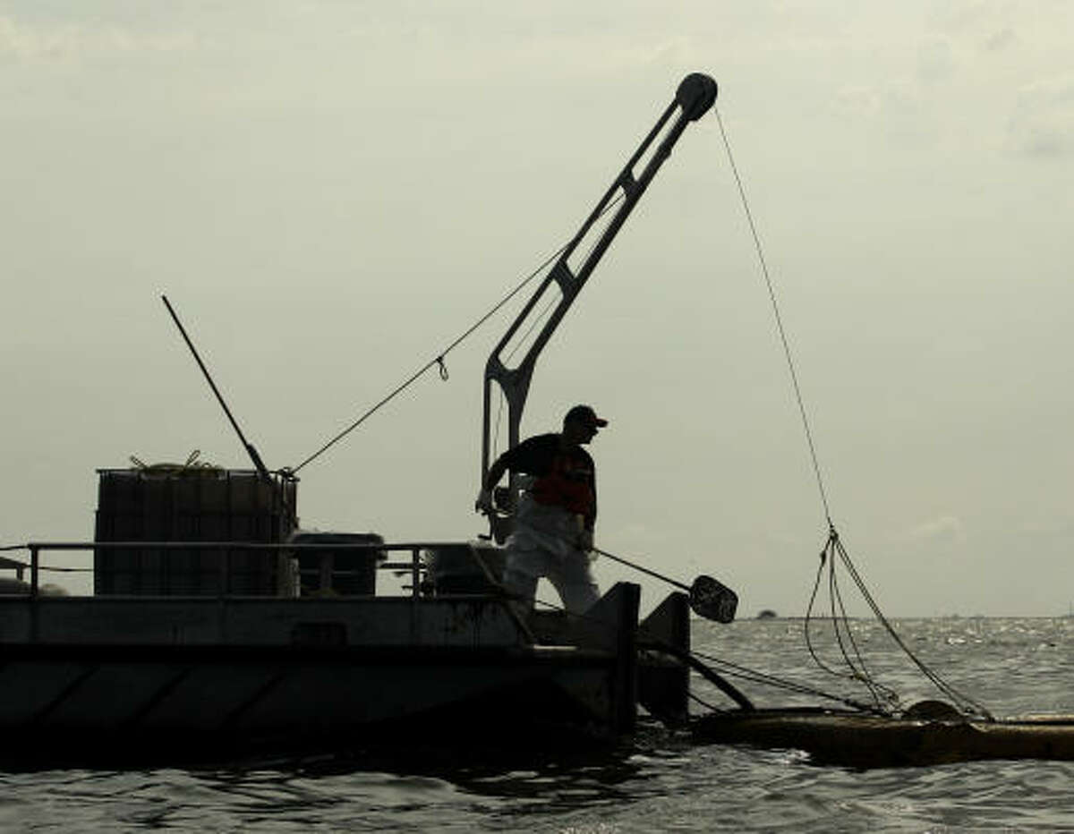 A worker cleans oil from the Deepwater Horizon oil spill from Barataria Bay off Cat Island, La., Friday, June 4, 2010.