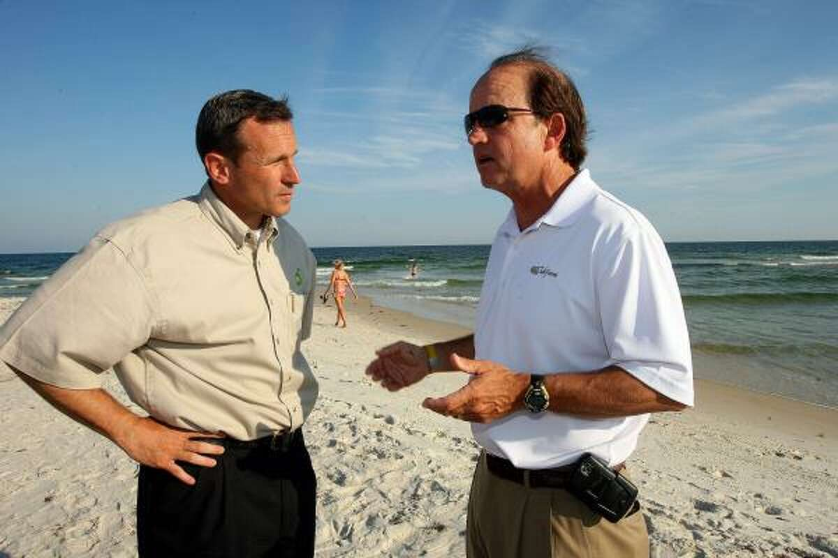 BP Chief Operating Officer Doug Settles, left, discusses the drill site as he tours the cleanup along the beaches of Gulf Shores, Ala., with Mayor Robert Craft on Tuesday.