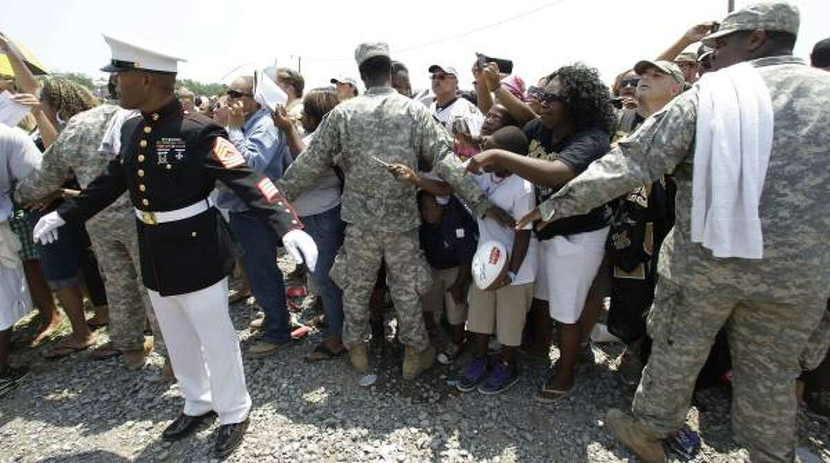 Marines and National Guardsmen help control the crowd in Buras, La., as the New Orleans Saints visit the area for a rally on Tuesday, June 8, 2010.