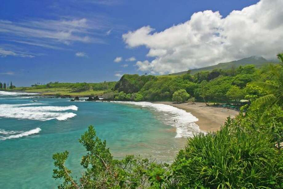 Hamoa Beach is on the east side of Maui near Hana, a less-developed part of this popular island. Hamoa Beach has sea cliffs and lush vegetation; the publc beach shares some facilities with the Hotel Hana Maui. Offshore is a little island with coconut trees. Photo: Ron Dahlquist, AP