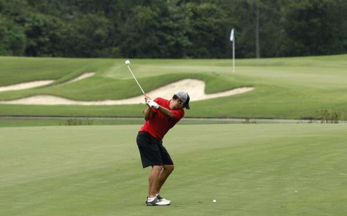Cowboys quarterback Tony Romo hits his approach shot on the 10th hole at the Club at Carlton Woods in The Woodlands.