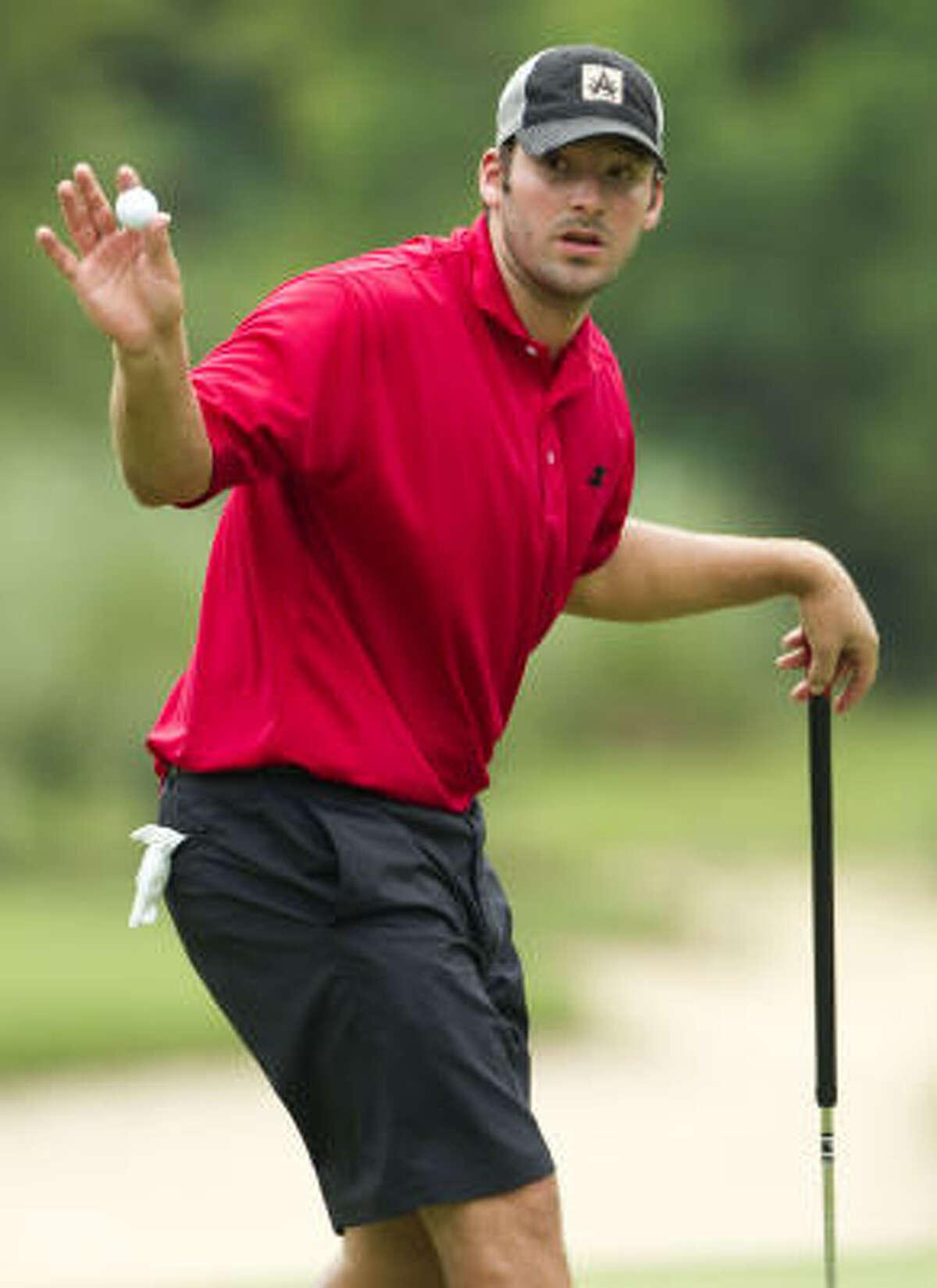Tony Romo reacts after hitting a putt on No. 16.