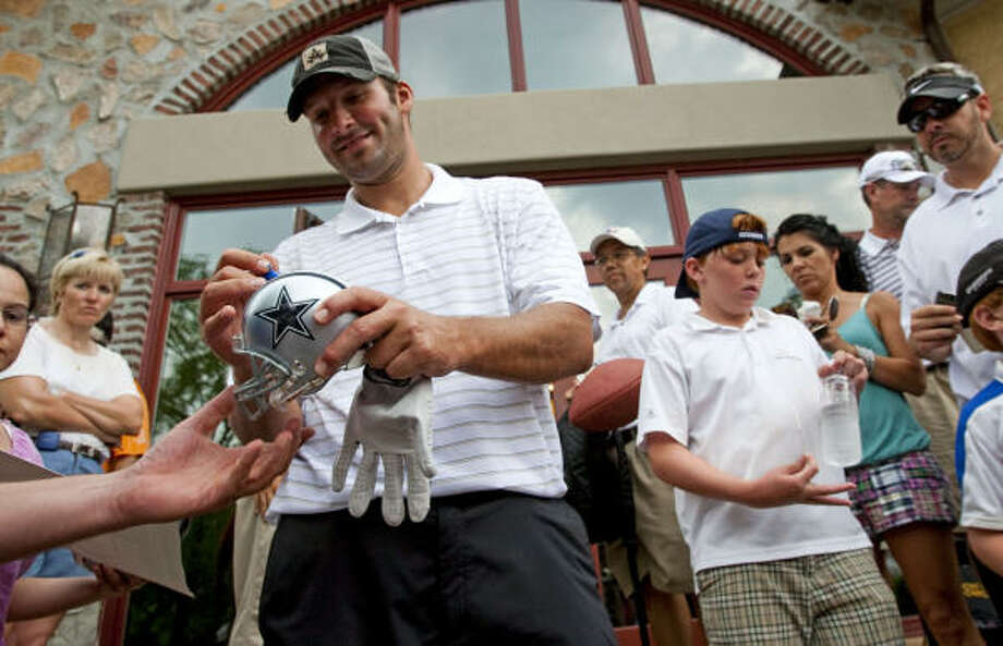Tony Romo autographs a miniature helmet after coming off the course during the U.S. Open Sectional qualifying tournament at Carlton Woods. Photo: Brett Coomer, Chronicle