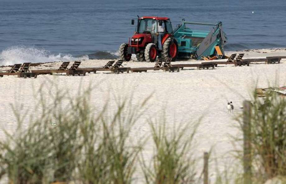 Workers drag the beach in Gulf Shores, Ala., Monday, June 7, 2010, to remove oil and seaweed that has washed up on the beach. Photo: Dave Martin, AP