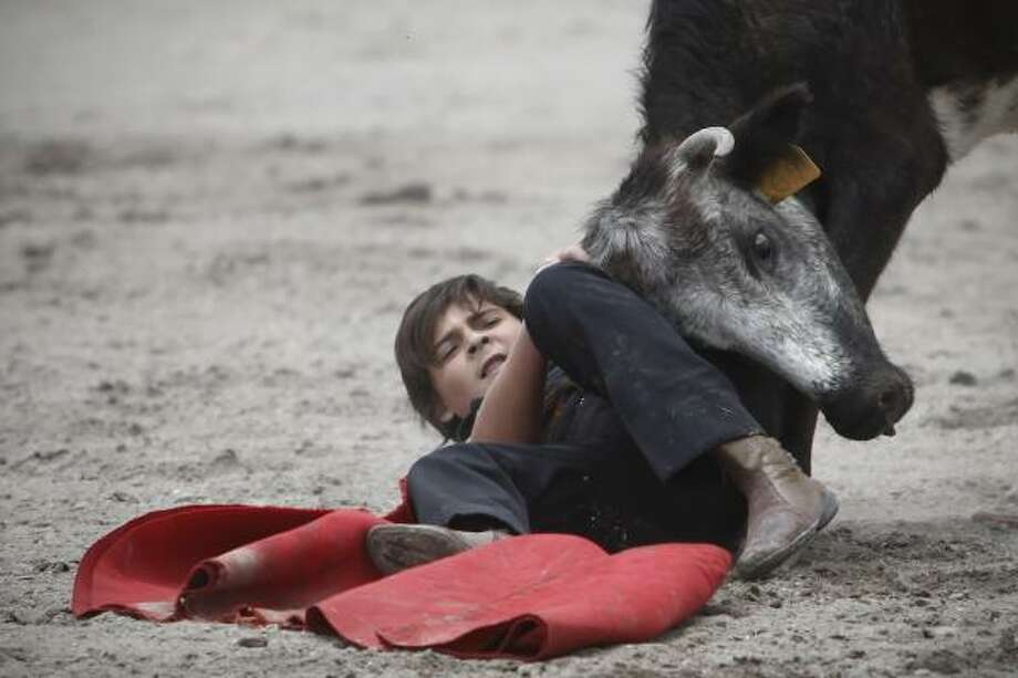 Franco-Mexican bullfighter Michel Lagravere, 12, known as Michelito,  is tossed by a young bull during a bullfight practice session in Tlaxcala, central Mexico, Saturday, June 5, 2010. Photo: Miguel Tovar, AP