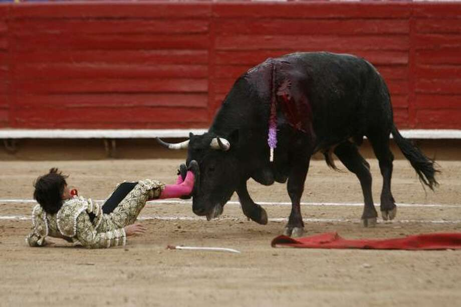 "French-Mexican bullfighter Michel Lagravere, 12, known as Michelito, is pushed by a bull after falling during a bullfight in the Plaza de Toros Mexico bullring in Mexico City, Sunday, June 6, 2010. The ""novillero"" lost his footing while facing his second bull on Sunday and was knocked around the sand by the 848-pound animal. Photo: Miguel Tovar, AP"