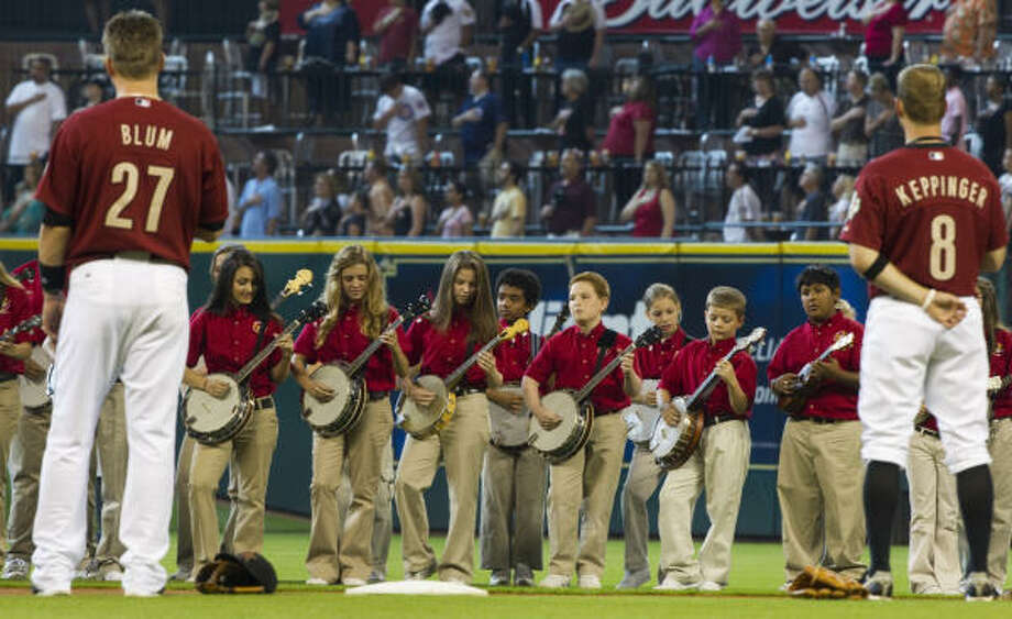 The Sagemont Baptist Church Banjo Band is flanked by Astros infielders Geoff Blum (27) and Jeff Keppinger as it performs the National Anthem before Sunday's game. Photo: Brett Coomer, Chronicle