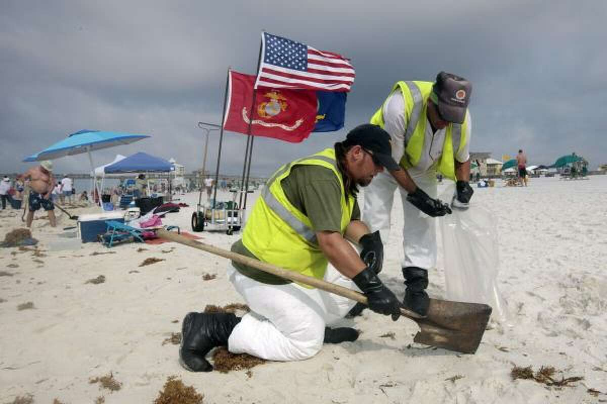 Oil cleanup workers hired by BP pick up tar balls Sunday as they work along Pensacola Beach, Fla.