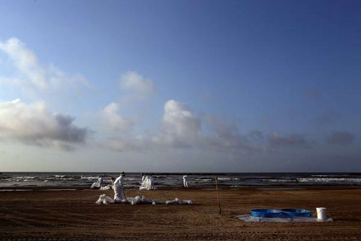 Workers clean oil from a public beach Sunday in Grand Isle, La.