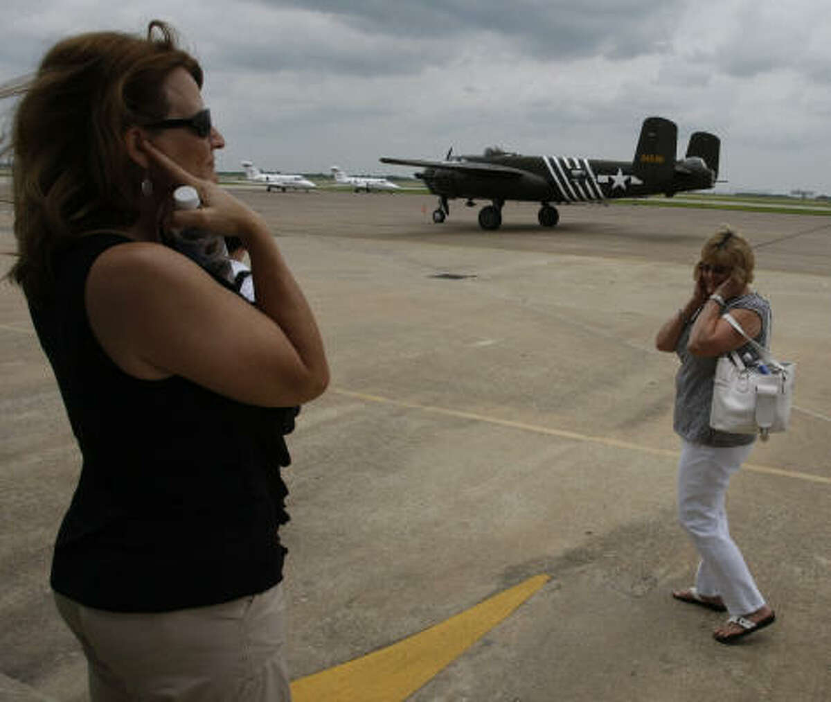 Tammy Pena, left, and Linda Lambert cover their ears as a B-25 fighter plane taxis into Ellington Field. On the eve of the 66th anniversary of D-Day, air buffs rode in war planes.