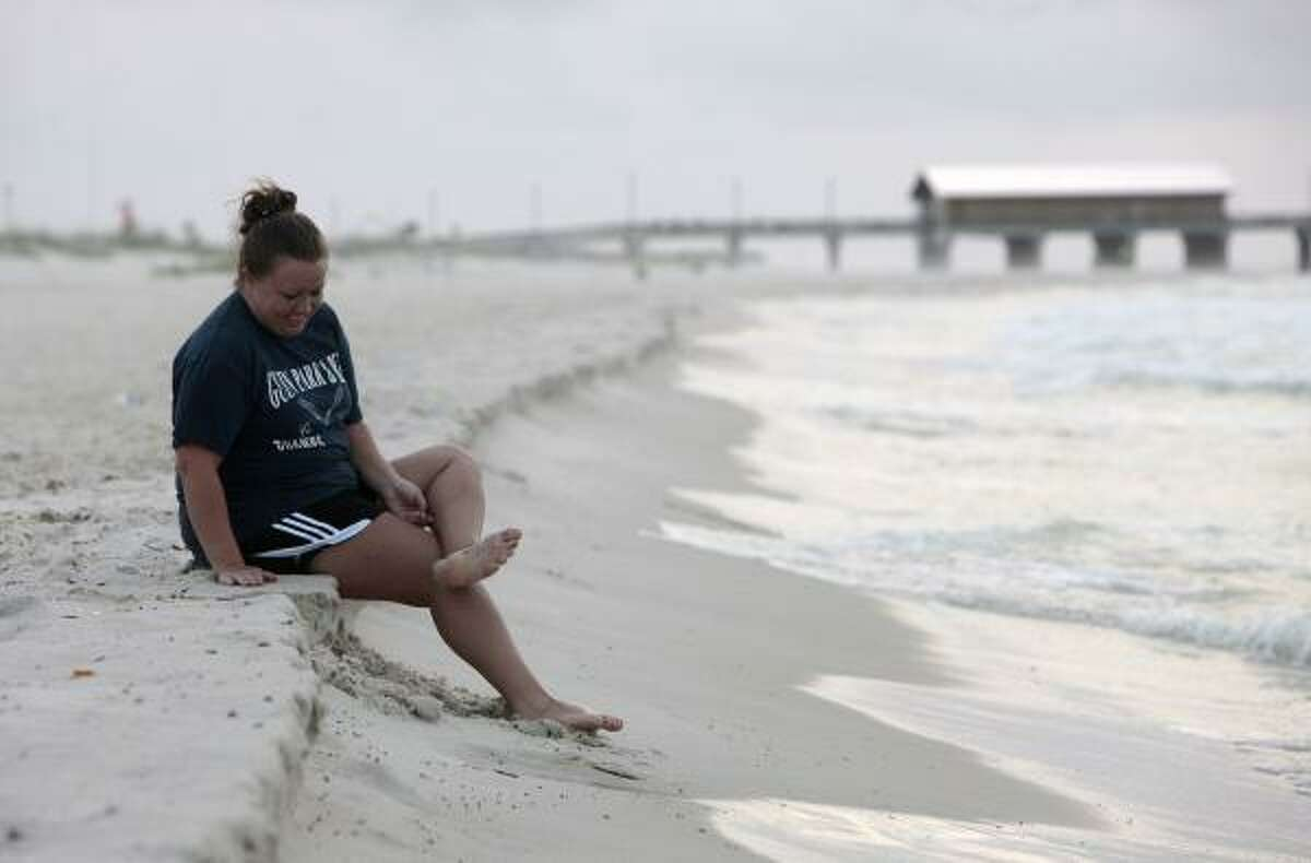 Brandi Wilson of Vernon, Ala., checks her feet for oil residue as she sits on the beach Saturday in Gulf Shores, Ala.