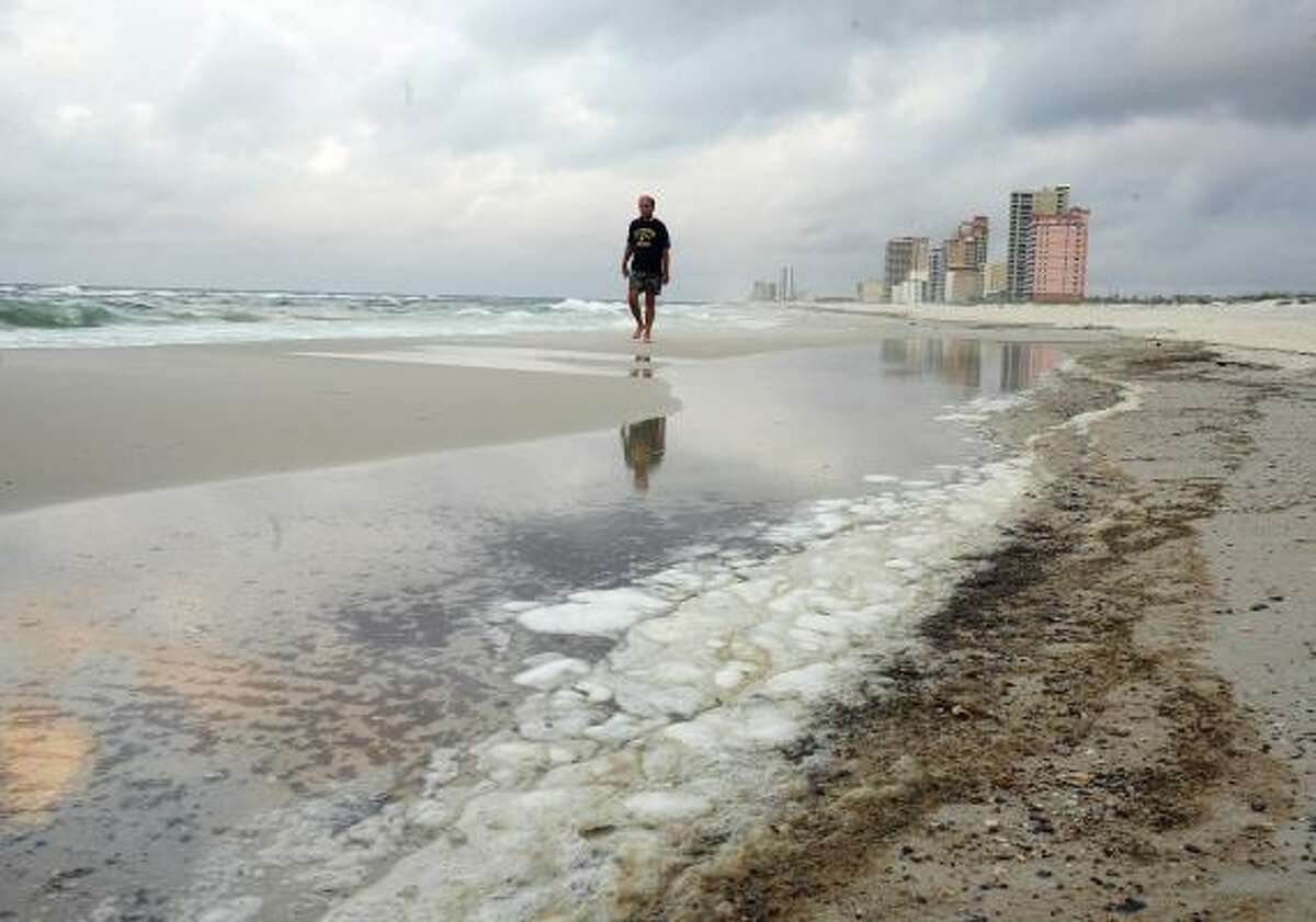 A man walks past oil residue on the beach in Gulf Shores, Ala.