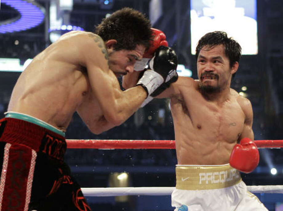 Manny Pacquiao, right, lands a punch against Antonio Margarito during the third round on Saturday night at Cowboys Stadium. Photo: David J. Phillip, AP