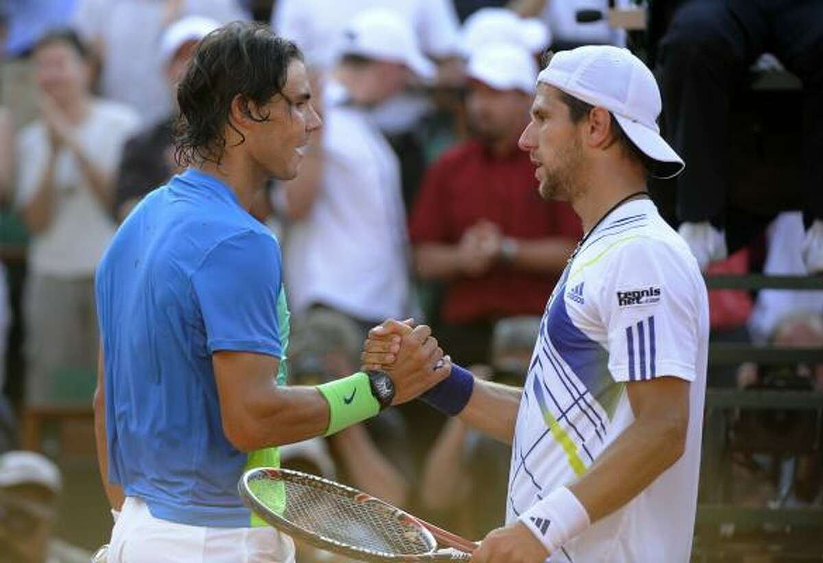Jurgen Melzer, right, shakes hands with Rafael Nadal after their match.