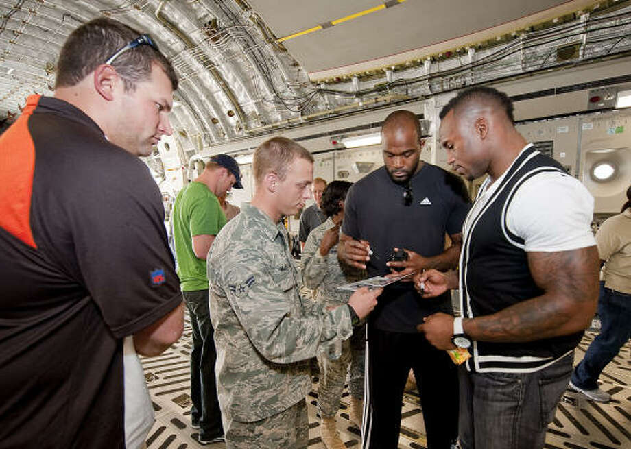 (From left) Cleveland's Joe Thomas, Dallas' Jason Witten (background), Houston's Mario Williams and San Francisco's Vernon Davis sign autographs for the crew of a C-17 cargo aircraft. Photo: DAVE GATLEY, USO Photo By DAVE GATLEY