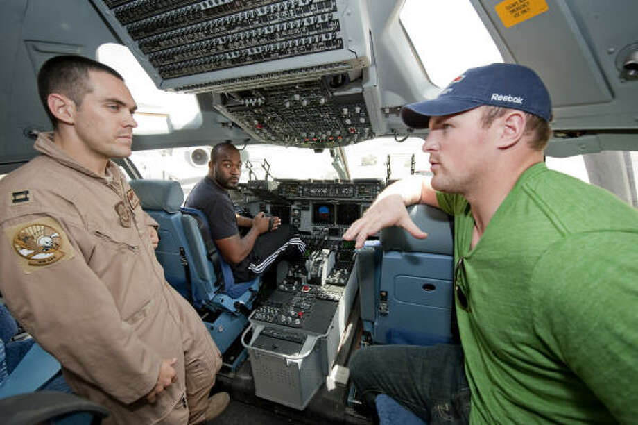 Mario Williams gets a bird's eye view from the pilot's seat of a C-17 while Jason Witten talks shop with Captain Paul Tucker. Photo: DAVE GATLEY, USO Photo By DAVE GATLEY