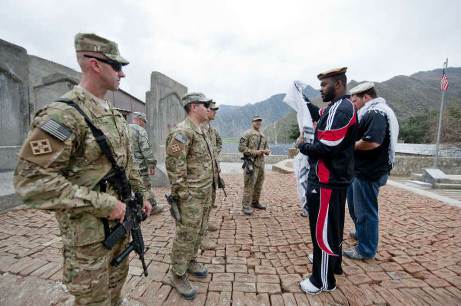 "Mario Williams and Joe Thomas try on the new Afghan scarfs and hats given to them by the troops while on a visit to FOB Blessing, a small base located in a ""hot-zone"" of activity and fighting. Photo: DAVE GATLEY, USO Photo By DAVE GATLEY"