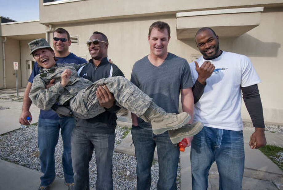Vernon Davis, second from left, gives this lucky captain a lift while fellow NFL Pro Bowlers Joe Thomas, left, Jason Witten, second from right, and Mario Williams get a good laugh. Photo: DAVE GATLEY, USO Photo By DAVE GATLEY