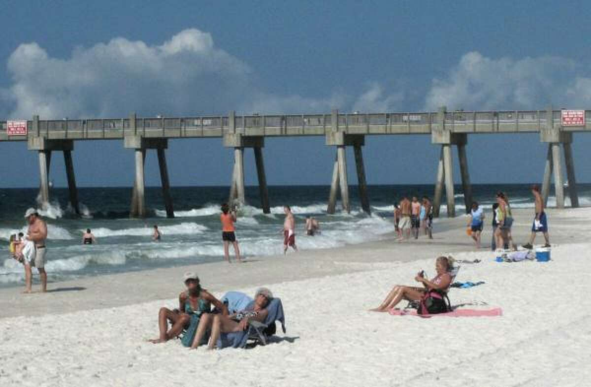 Beachgoers relax and walk on Pensacola Beach, Fla. Friday morning. Waves of gooey tar blobs were washing ashore in growing numbers on the white sand of the Florida Panhandle Friday as a slick from the BP spill drifted closer to shore.