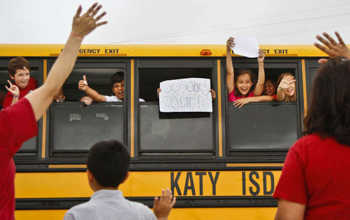 Fourth-grade students, Rex Stamatis, 10, Brian Castro, 10, Kelly Escovy, 10, Hannah Watson, 10, and Sueda Ay, 10, wave to teacher Doris Ortiz and her son Ryan, 10, and teacher Joanna Everett while waiting for the school bus to take off after the last day of school at Stanley Elementary School in Katy.