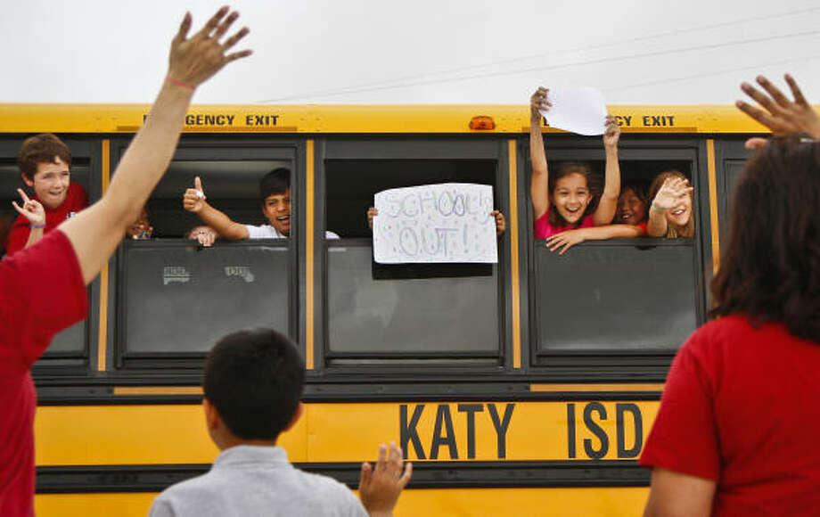 Fourth-grade students, Rex Stamatis, 10, Brian Castro, 10, Kelly Escovy, 10, Hannah Watson, 10, and Sueda Ay, 10, wave to teacher Doris Ortiz and her son Ryan, 10, and teacher Joanna Everett while waiting for the school bus to take off after the last day of school at Stanley Elementary School in Katy. Photo: Michael Paulsen, Chronicle