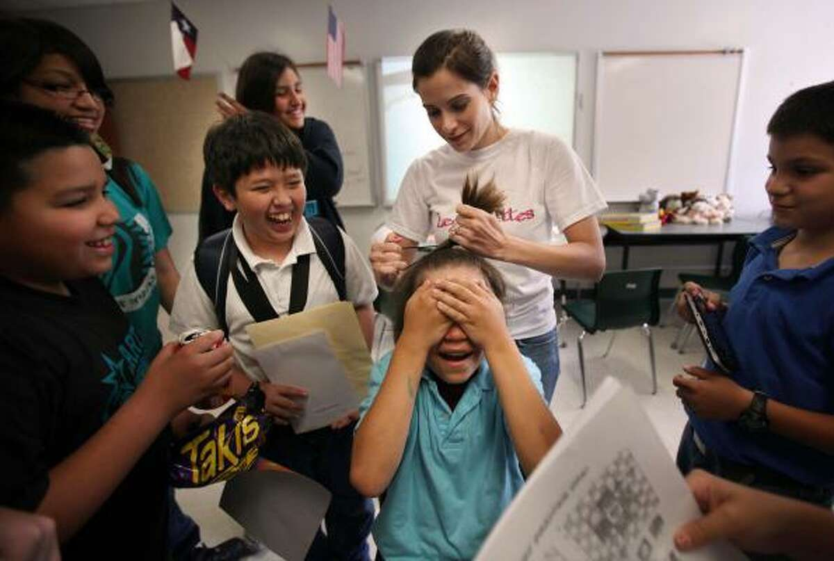 Victor Valdez, 11, and Vincent Tagavelou, 11, laugh as Amanda Psarovarkas, a 6th grade Social Studies teacher, pulls back the hair of Mark Sedgwic, 12, who spent all year hiding his face with long hair and promised he would pull it back on the last day of school at Carter Lomax Middle School in Pasadena.