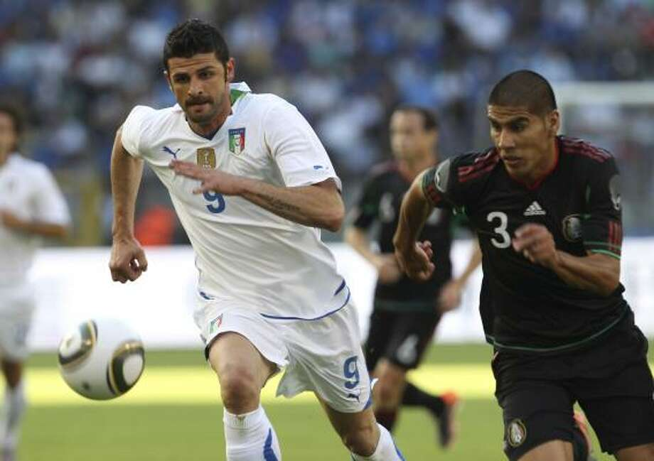 Italy's Vincenzo Iaquinta, left, runs after the ball with  Mexico's Carlos Salcido. Photo: Yves Logghe, AP