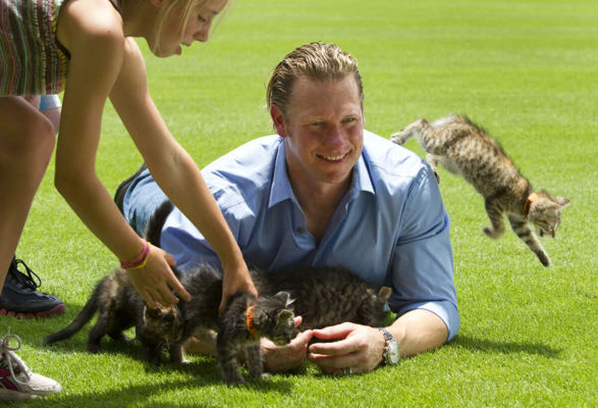 Kittens scatter as Houston Astros outfielder Jason Michaels poses for a photo during the Houston Astros Player & Pet Calendar shoot at Minute Maid Park in Houston. For the third year, the Astros are teaming up with the Houston Humane Society to help raise funds for the organization. Astros players poses for photos with adoptable pets from the Humane Society.