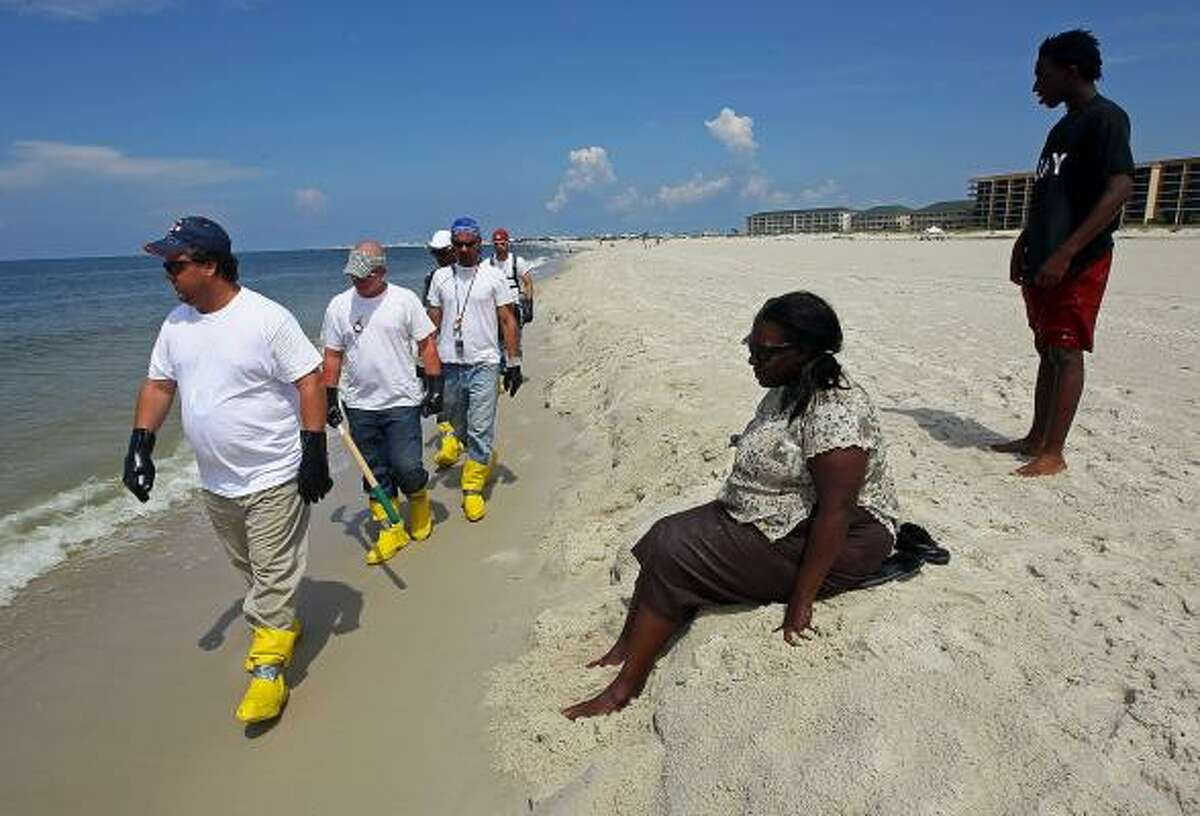 As Gwen Benjamin and Shun Benjamin watch, contract workers patrol the beach to pick up oil that washed ashore on a public beach on June 2, 2010, in Dauphin Island, Ala. Oil believed to be from the Deepwater Horizon oil rig accident began to appear Juen 1 on the shores of Alabama.