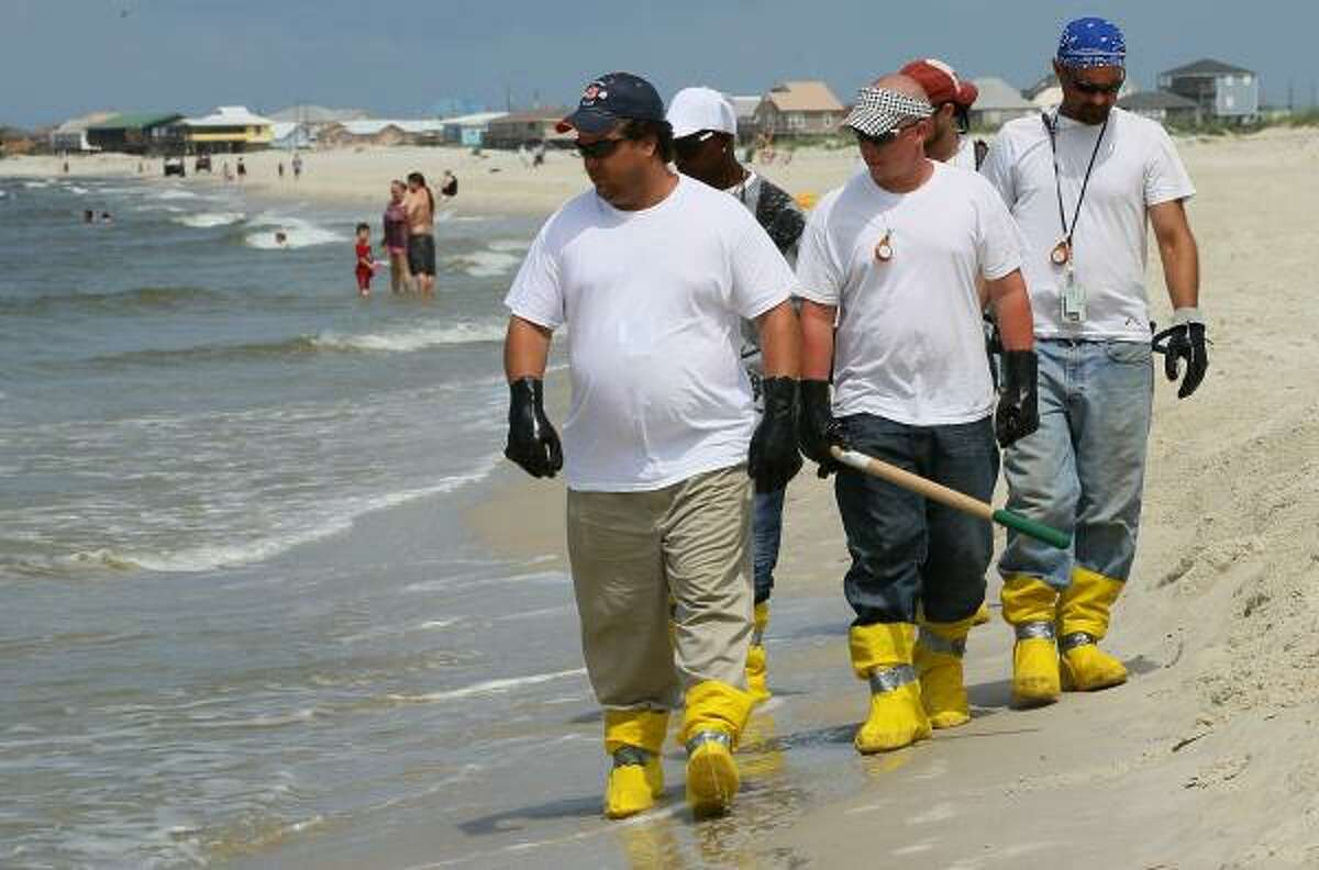 Contract workers patrol the beach to pick up oil that has wash ashore on a public beach on June 2, 2010 in Dauphin Island, Ala.