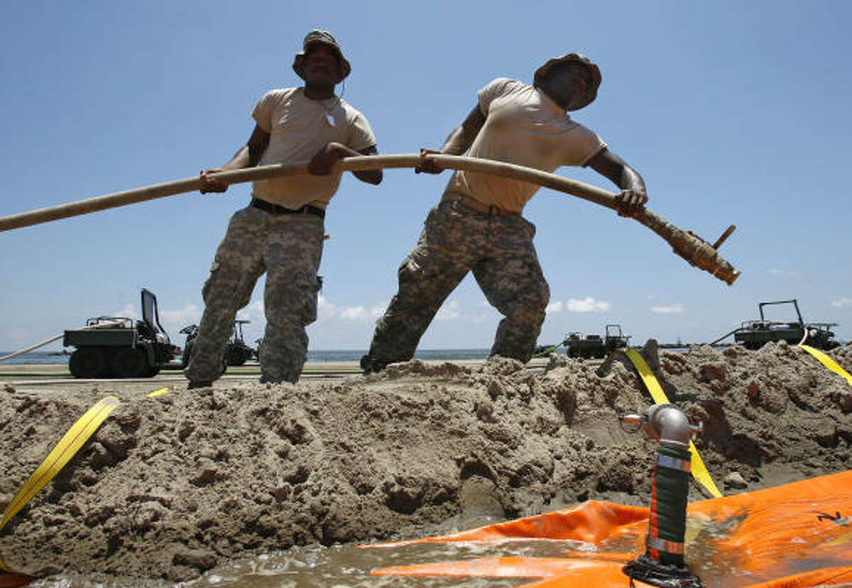 Louisiana National Guard Specialists Alvin Dunn and Bryan Jones carry a hose to fill a tiger dam on a beach in Grand Isle, La., Tuesday, June 1, 2010. When completed, the water-inflated dam is expected to protect the island's entire shoreline along the Gulf of Mexico.