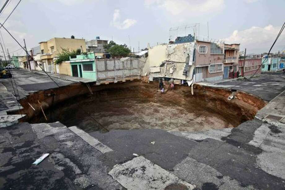 A sinkhole covers a street intersection in downtown Guatemala City. Authorities are trying to determine what caused the circular hole. Photo: Rodrigo Abd, AP
