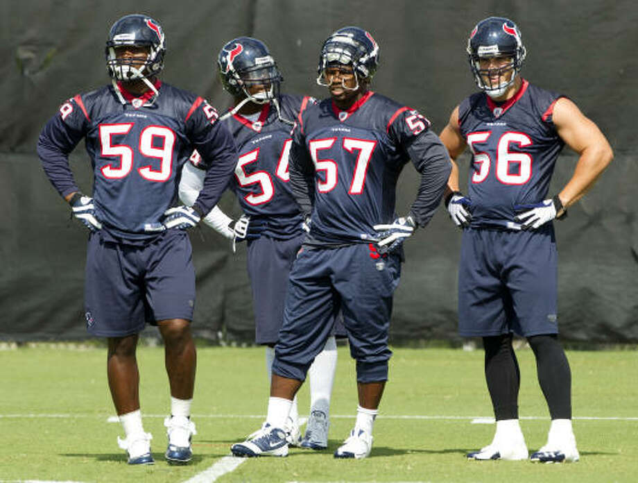 Texans linebacker DeMeco Ryans (59), Zac Diles (54), Kevin Bentley (57) and Brian Cushing (56) stand together between drills. Photo: Brett Coomer, Chronicle