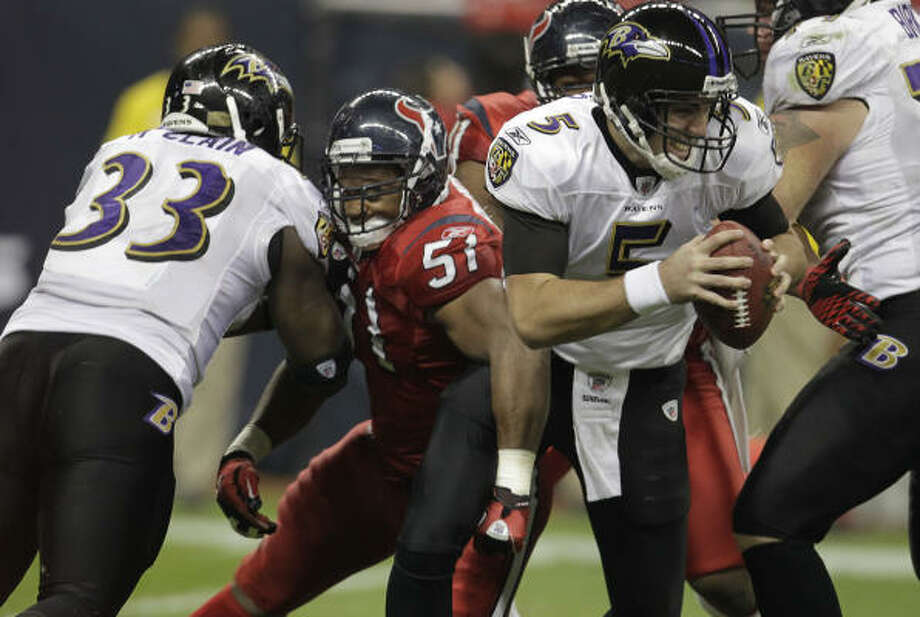 Ravens quarterback Joe Flacco (5) gets sandwiched and tangled up by Texans linebacker Kevin Bentley (57) during the third quarter. Photo: Karen Warren, Chronicle
