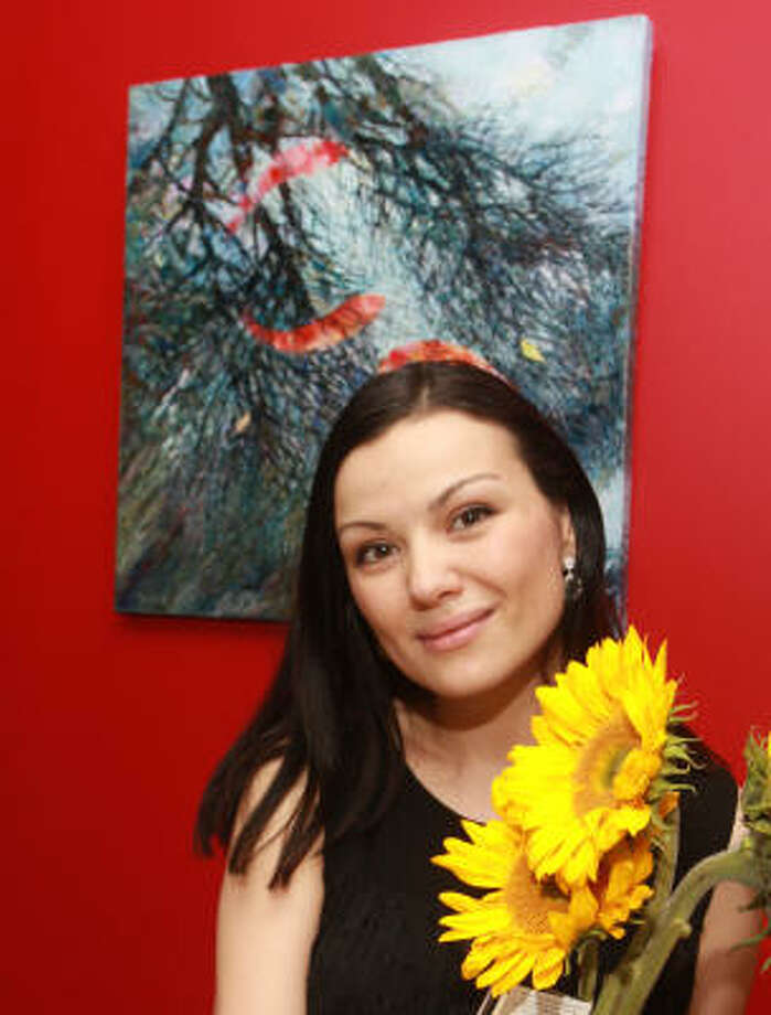 Artist Anna Ataeva in front of her painting, Koi Dance, one of the artworks that inspired the On Flowers event at SoVino. Photo: Gary Fountain, For The Chronicle
