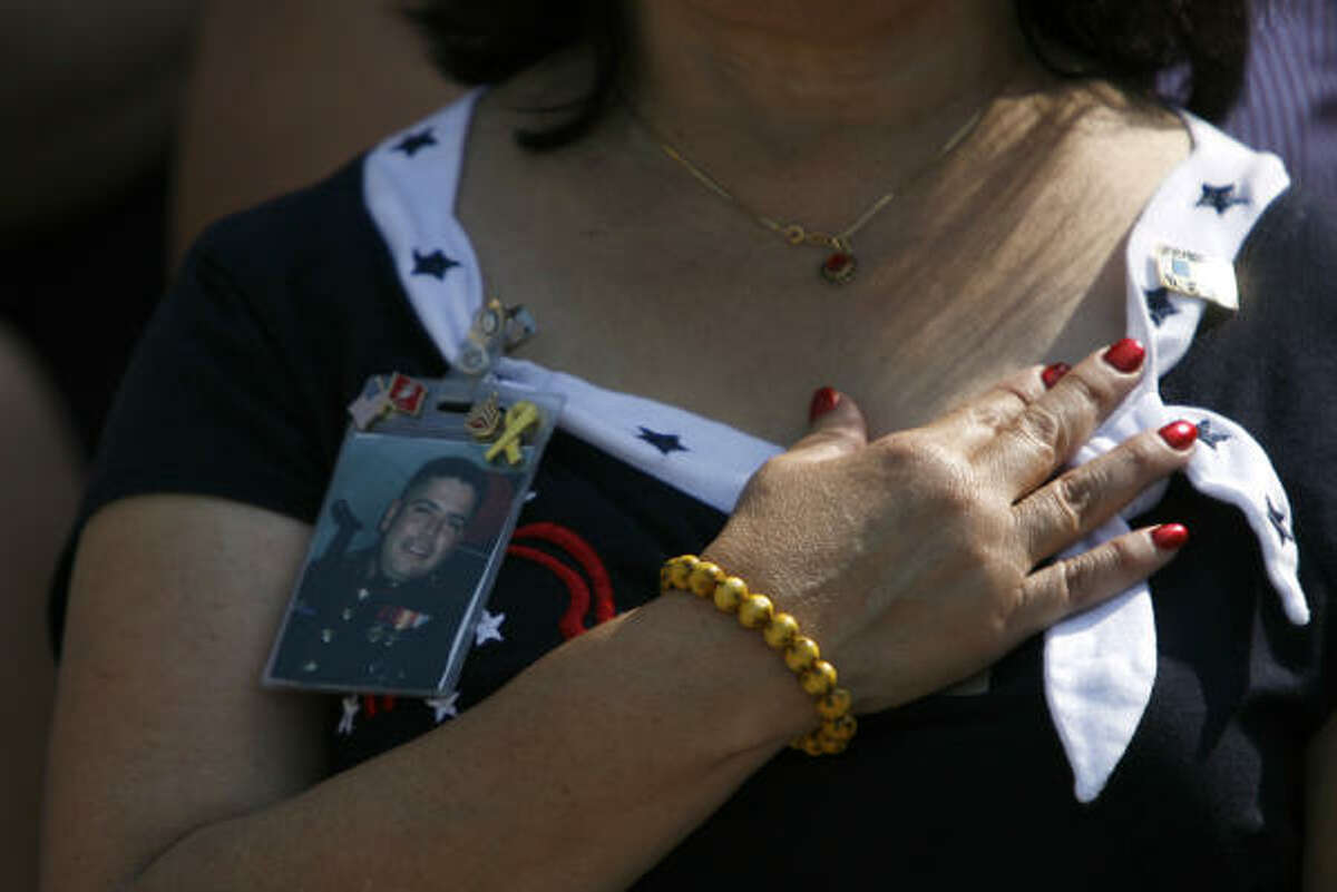 Mary Lucario holds her hand over her heart during the Pledge of Allegiance during the Houston ceremony. She's wearing a photo of her son, Staff Sgt. Vincent Lucario, who is serving on the USS Pelelieu.
